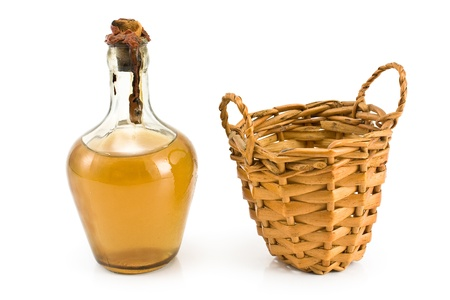 Old sealed bottle of white wine with basket isolated on white photo