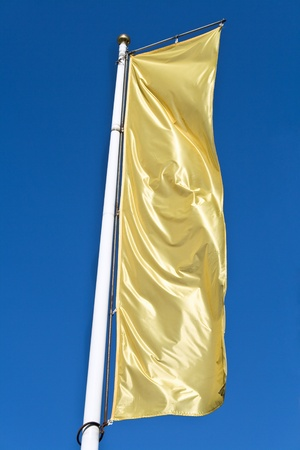 Empty vertical banner golden flag over blue sky Stock Photo