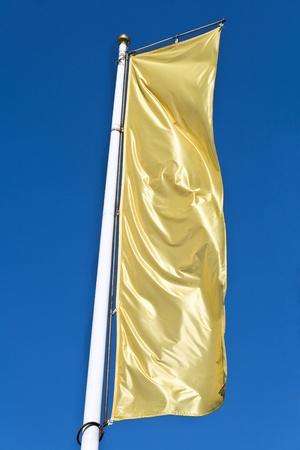 Empty vertical banner golden flag over blue sky Stock Photo