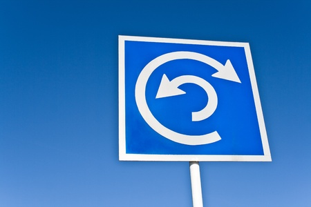 Roundabout sign over blue sky photo