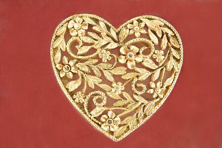 Golden heart jewelry  on red background photo