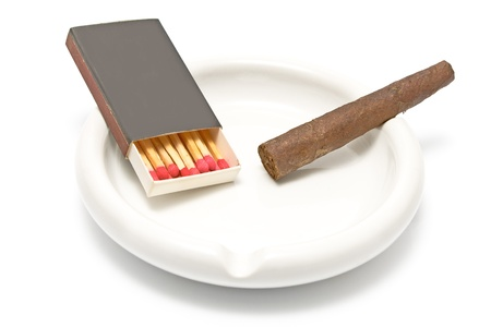 Cigar with matches and ashtray on white photo