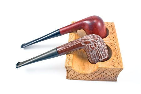 Two tobacco pipes on wooden holder isolated on white photo