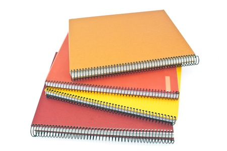 Stack of spiral notebooks isolated on white photo