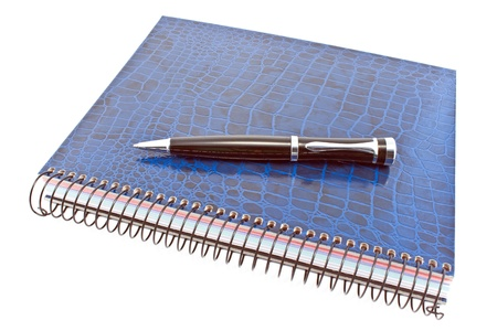 Blue spiral notebook with pen isolated on white photo