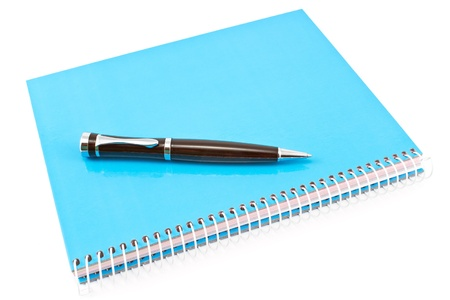Pen on blue spiral notebook isolated on white photo