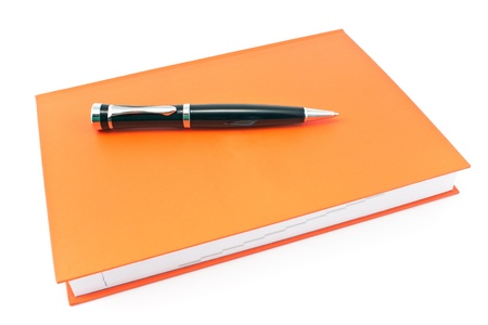 Pen on  red notebook isolated on white photo