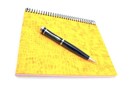 Pen on yellow spiral notebook isolated on white photo