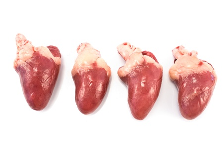 inwards: Four raw chicken hearts isolated on white