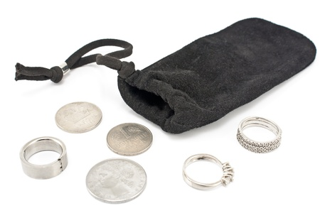 jewelle: Black velvet sack with silver rings and coins on white