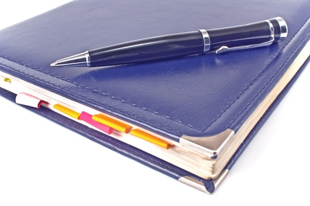 Pen and blue notebook on white