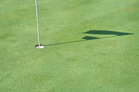 Hole and shadow of golf flag waving photo