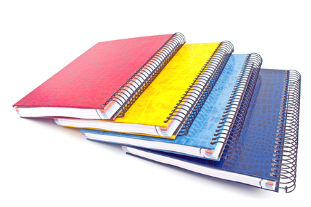 Stack of colorful spiral notebooks isolated on white photo