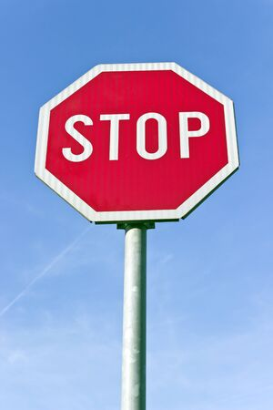 Stop road traffic sign over blue sky photo