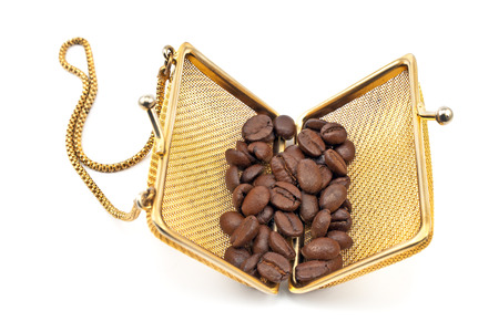 Golden purse with coffee beans isolated on white photo