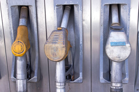 unleaded: Old used gas pump nozzles in service station