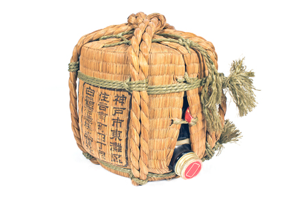 Traditional wicker container of sake isolated on white photo