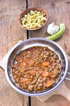 Minced meat sauce with vegetables cooked in pan with pasta photo