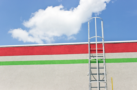 Safety metal ladder to the roof over blue sky photo