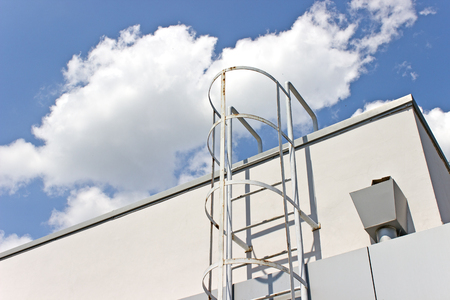 Safety metal ladder to the roof and  blue sky photo