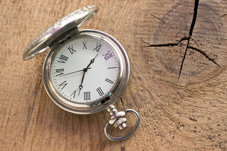 Silver pocket watch on wooden background photo