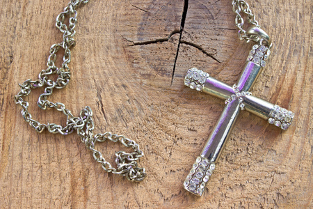 Silver christian cross with small diamonds on wooden background photo