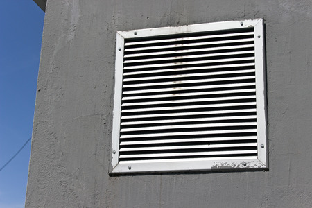 Vent window on gray concrete wall with blue sky photo