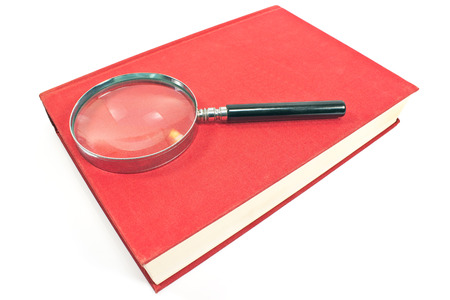 Antique magnifying glass on red book isolated on white photo