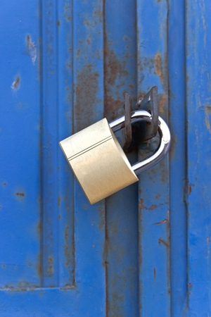 Padlock on old blue metal door photo