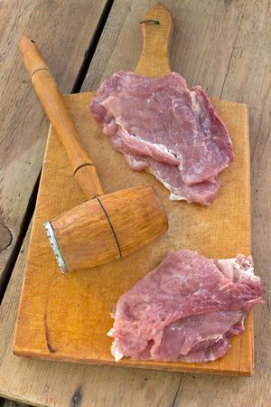 slabs: Tenderize slabs of meat on wooden board