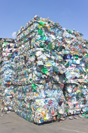 recycle waste: Stack of plastic bottles for recycling against blue sky Stock Photo