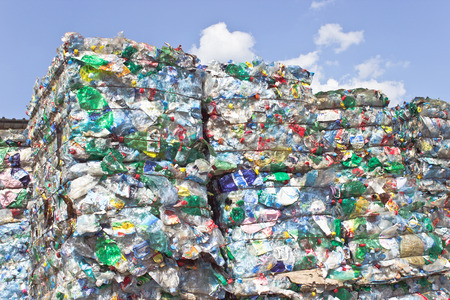 scrap trade: Stack of plastic bottles for recycling against blue sky Stock Photo