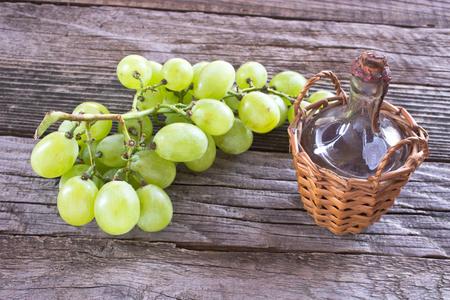 white grape: Old sealed bottle of wine and white grape on wooden background