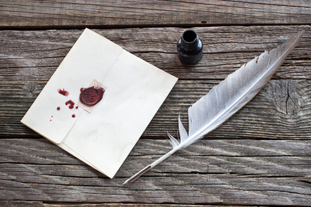 pen and paper: Wax sealed letter with quill on wooden background