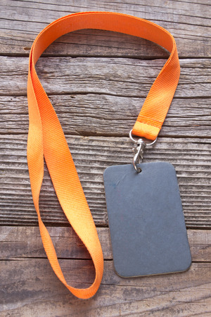 credential: Blank ID card tag on wooden background