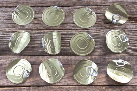 lids: Tin can lids with opener on wooden background Stock Photo
