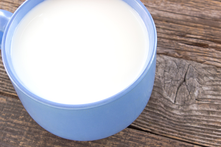 pasteurized: Cup of milk on wooden background