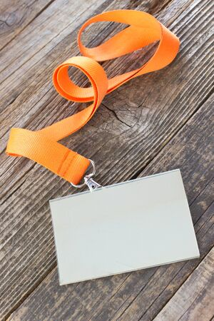 credential: Blank  ID card tag with ribbon on wooden background