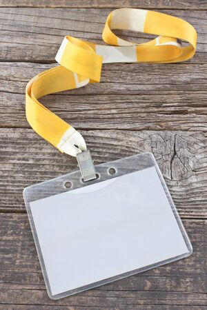 Blank ID card tag and yellow ribbon on wooden background