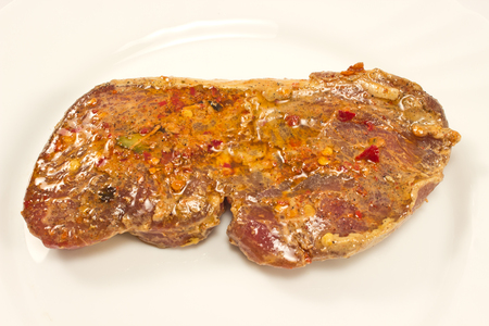 marinade: Raw steak with marinade in white plate