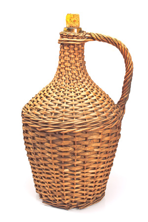 Old demijohn wicker wrapped glass bottle isolated on white Stock Photo