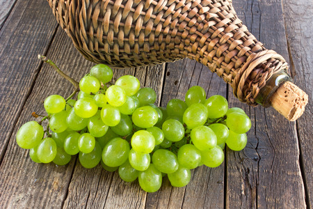 White grape with old wicker wrapped glass bottle on wooden table Stock Photo
