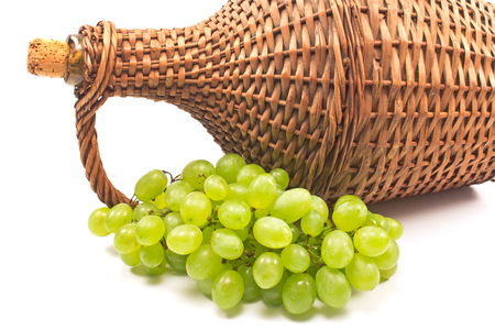 White grape with old wicker wrapped glass bottle on white background
