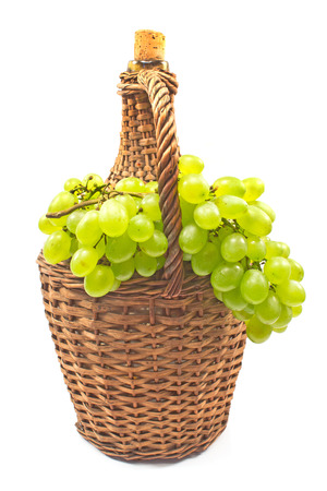 White grape with old wicker wrapped glass bottle isolated on white