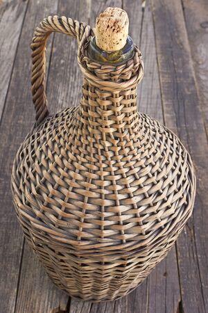Old demijohn wicker wrapped glass bottle on old  wooden table