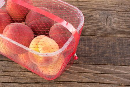Peaches packaged for sale on wooden background