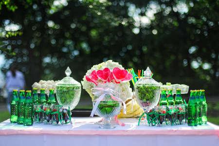 candy bar: Verde barra de caramelo de la boda con corazones rojos y botellas para bebidas Foto de archivo