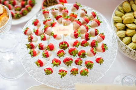 candy bar: Fresas con chocolate blanco en el plato en la barra de chocolate