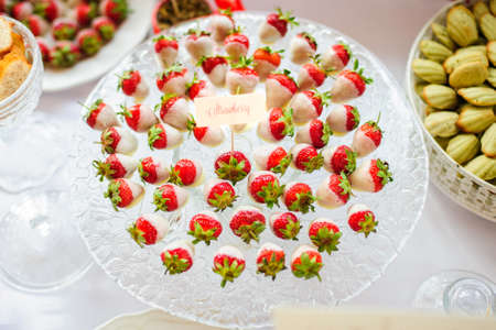Strawberries with white chocolate on the plate in candy bar photo