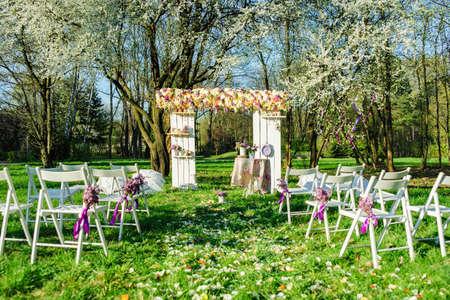 Alles is klaar voor een huwelijksceremonie in bloeiende tuin in zonnige lentedag Stockfoto